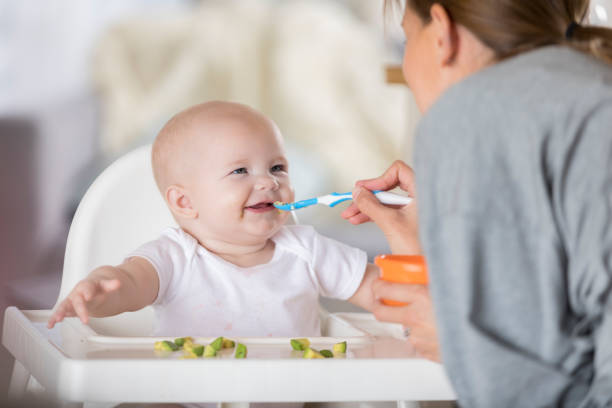 adorable baby in high chair laughs while being spoon fed - nutrire foto e immagini stock