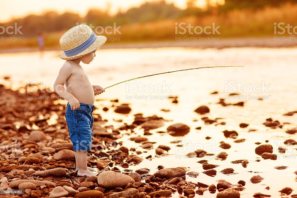Adorable baby on river with fishing-rod and fishing stock photo