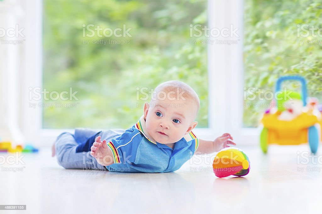 Adorable baby playing on floor next big garden view window stock photo