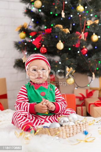 Santa helpers. Adorable baby elf standing with friend at Christmas tree with gifts, free space