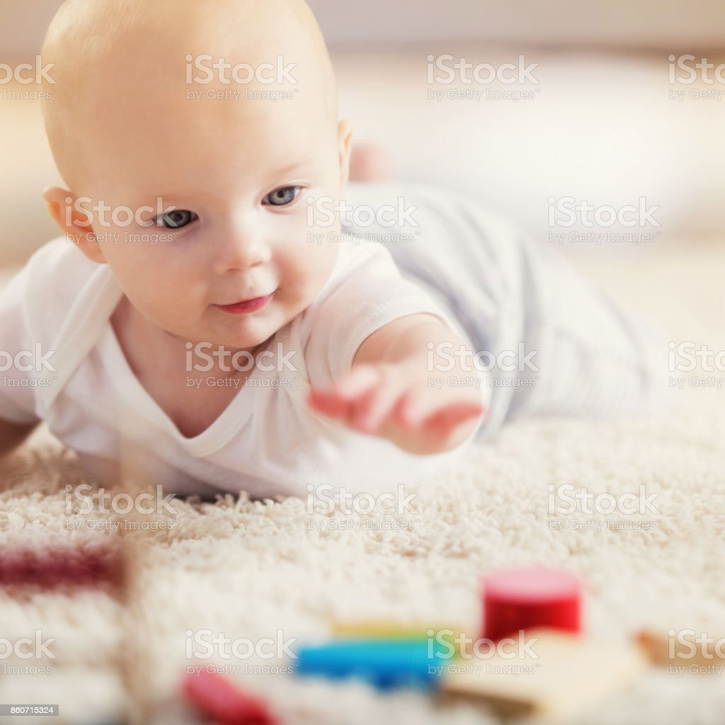 Adorable baby reaches for wooden blocks during tummy time stock photo