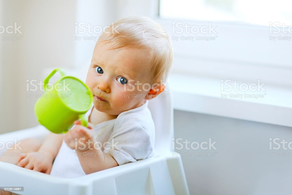 Adorable baby  sitting in chair and holding cup stock photo