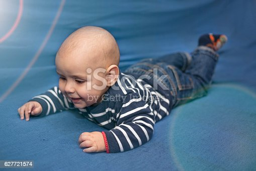 istock Adorable baby. Six month old Baby lying on blue blanket 627721574