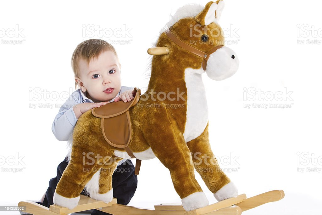 Adorable baby trying to stand with a hobbyhorse's help royalty-free stock photo