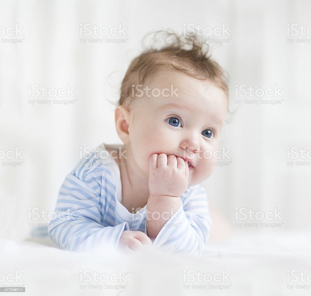 Adorable baby with beautiful blue eyes playing on her tummy royalty-free stock photo