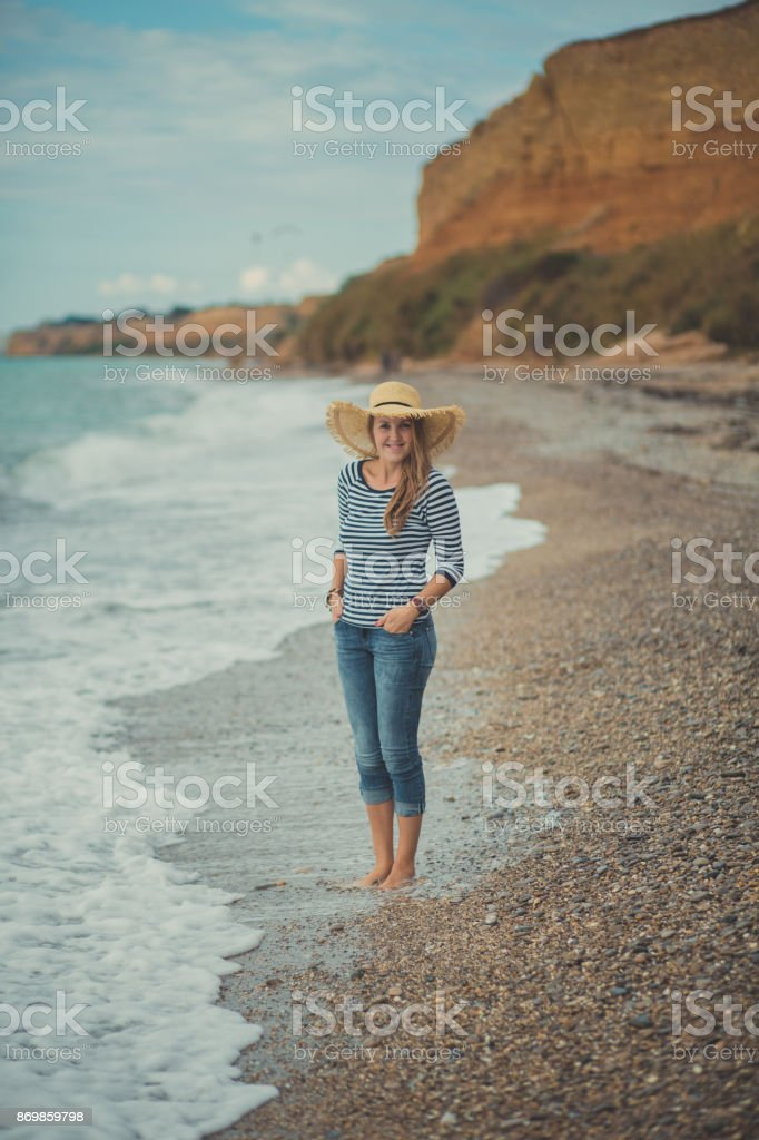 Adorable beauty lady woman eve walking posing alone on beach sea side ocean vacation wearing modish blue jeans shirt and huge hat with touchy landscape of sand cliff cape stock photo