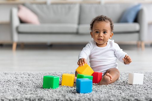 Adorable Black Infant Baby Playing With Stacking Building Blocks At Home While Sitting On Carpet In Living Room, Portrait Of Cute African American Child Using Colorful Constructor Toys, Copy Space