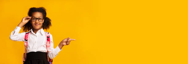 Adorable Black Schoolgirl Pointing Finger Aside, Studio, Panorama Look Here. Adorable Black Schoolgirl Pointing Finger Aside Advertising Something Standing Over Yellow Studio Background. Empty Space, Panorama nerd hairstyles for girls stock pictures, royalty-free photos & images