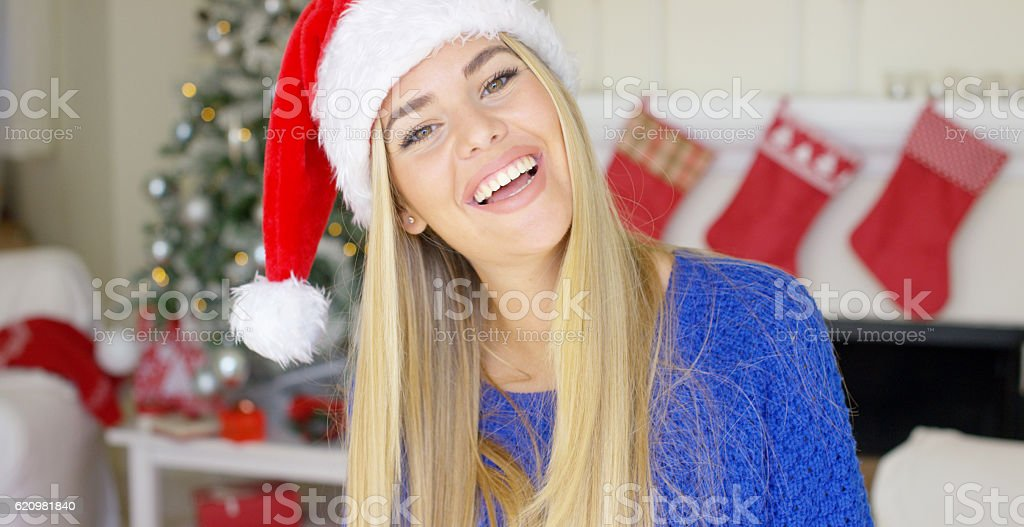 Adorable blond girl in christmas hat in her home foto royalty-free