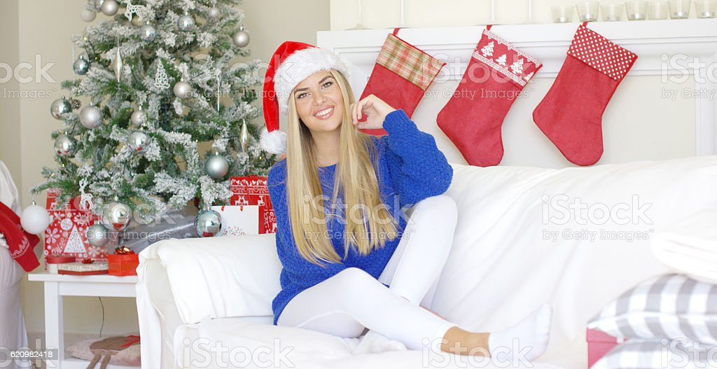 Adorable blond girl sitting on sofa in Santa Claus hat foto royalty-free