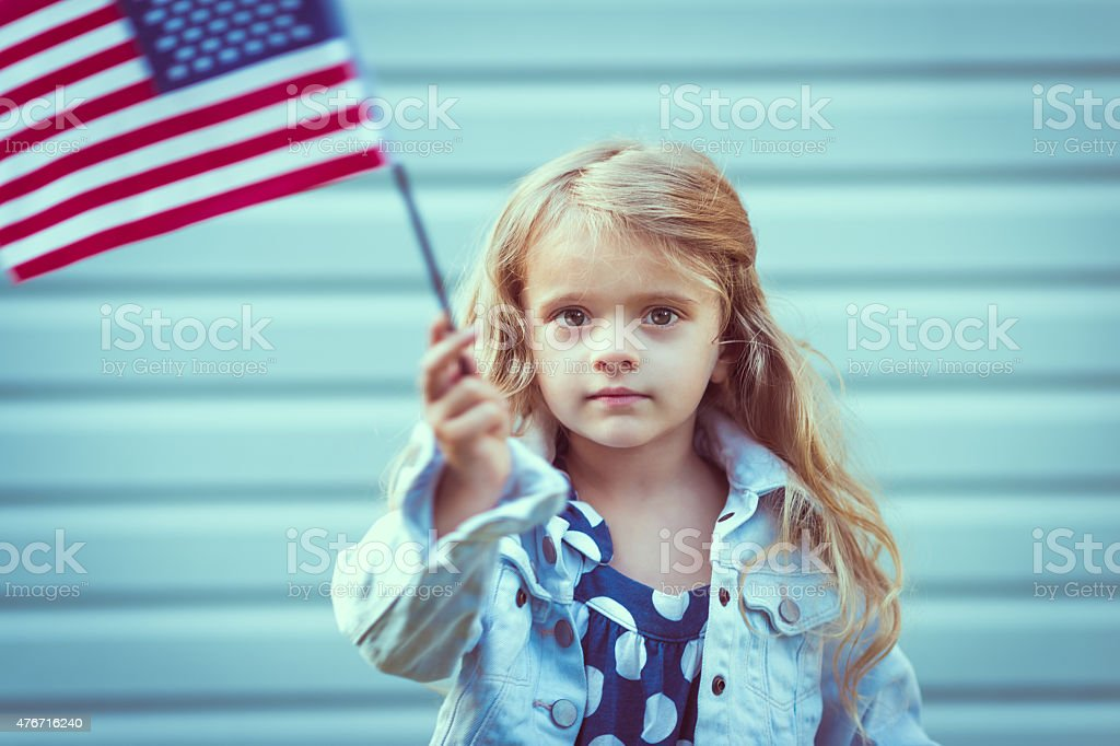 Adorable blond little girl with long hair holding american flag stock photo