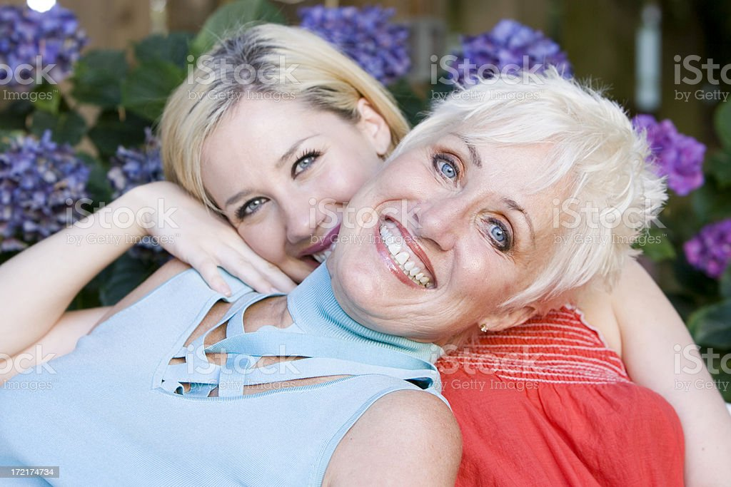 Adorable Blond Mother and Daughter Portrait Outside with Flowers royalty-free stock photo