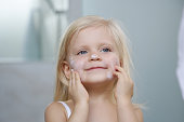 Adorable blonde caucasian toddler girl applying cream on her face