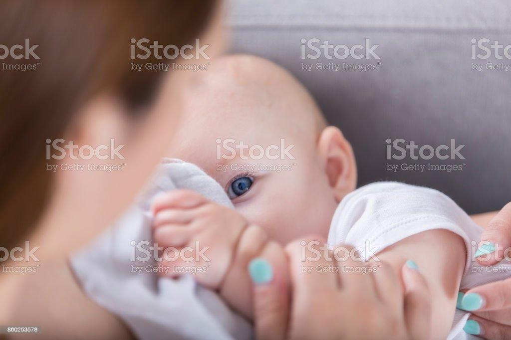 Adorable bebé de ojo azul Mira mamá durante la lactancia - foto de stock