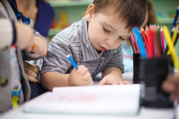Adorable boy drawing with color pencil at playschool stock photo