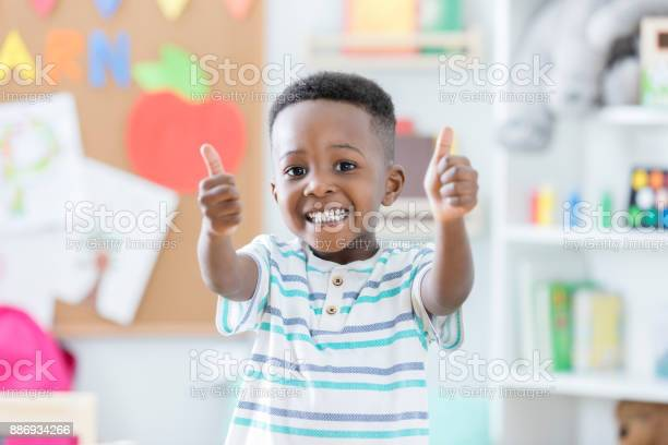 An adorable preschool age little boy smiles for the camera as he stands in his preschool classroom and gives a thumbs up.  He loves school!