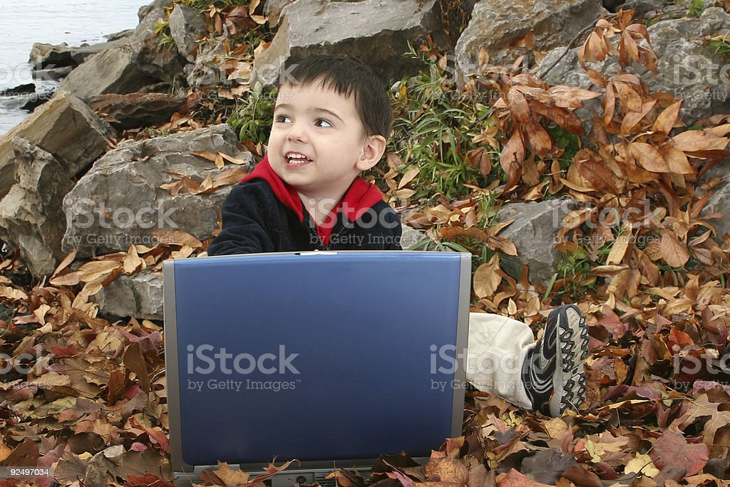 Adorable Boy In Leaves with Laptop royalty-free stock photo