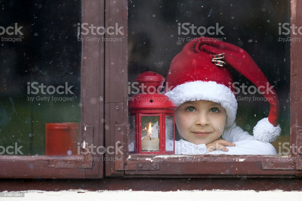 Adorable boy, looking through window, waiting for Santa stock photo