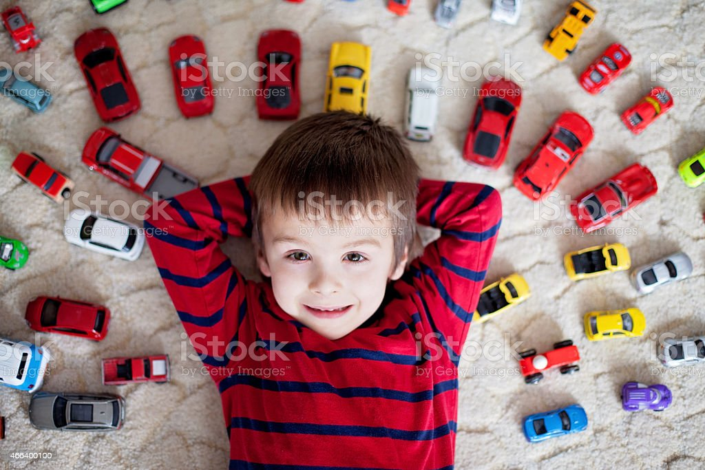 Adorable boy, lying on the ground, toy cars around him stock photo