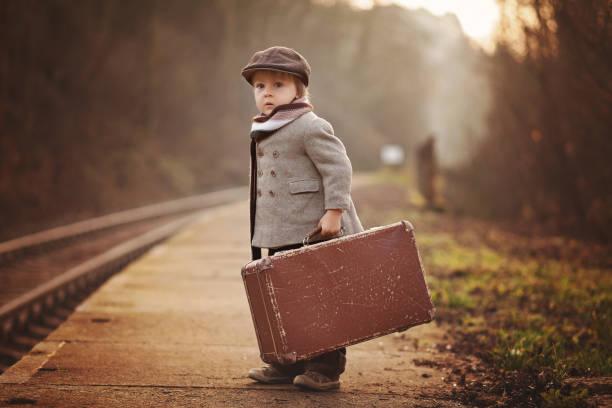 Adorable niño en una estación de ferrocarril esperando el tren con la maleta y oso de peluche - foto de stock