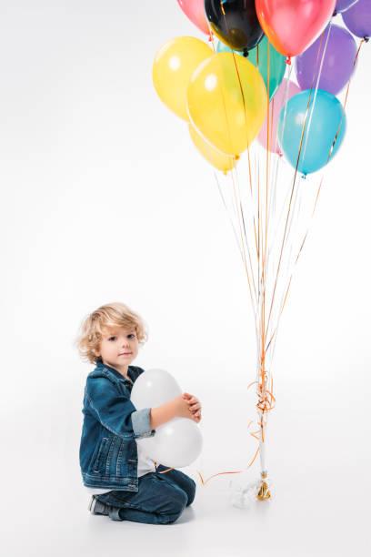 entzückende junge sitzt mit bündel von ballons auf weiß - ballonhose stock-fotos und bilder