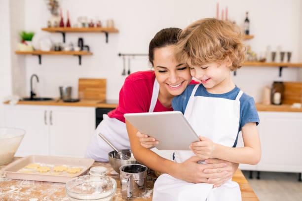 Entzückende Junge mit Touchpad und seine glückliche Mutter diskutieren Video-Rezept – Foto