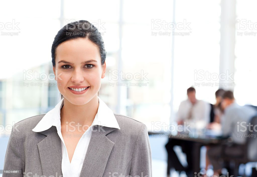 Adorable businesswoman standing in front of her team while working stock photo