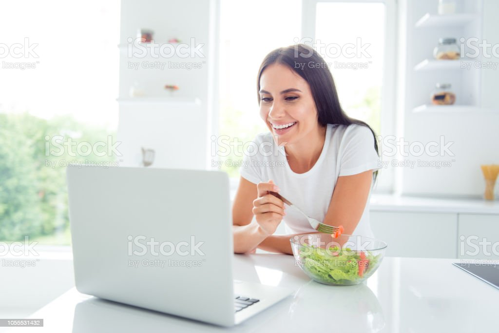 Adorable charming pretty beautiful funny stylish well-groomed girl holding fork in hand, tasting yummy tasty green salad, snack in modern light white interior, watching hilarious humorous tv comedy stock photo