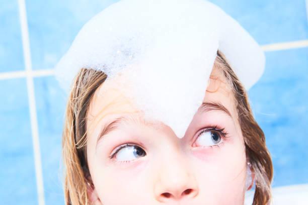 entzückenden kind blondes mädchen mit shampoo schaum auf haar bad zu nehmen. - mädchen dusche stock-fotos und bilder