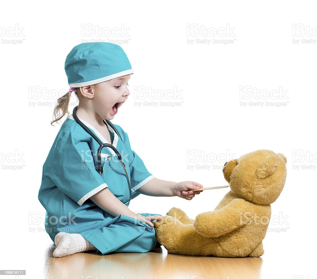 Adorable child dressed as doctor playing with toy over white...
