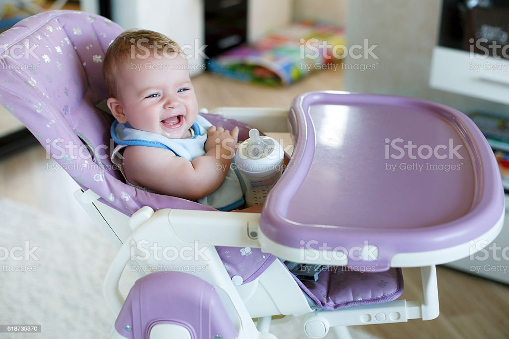 Adorable child drinking from bottle. stock photo