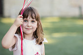 Cheerful girl holding strings from balloons