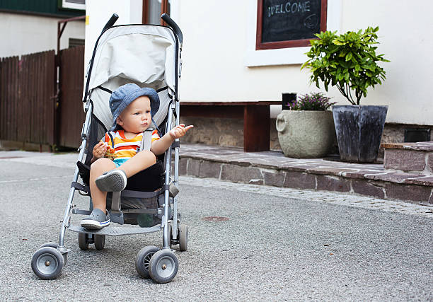 Adorable child toddler in a stroller on the street. stock photo