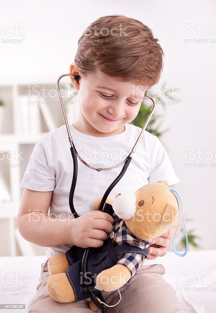 Adorable child with stethoscope of doctor examining teddy bear stock photo