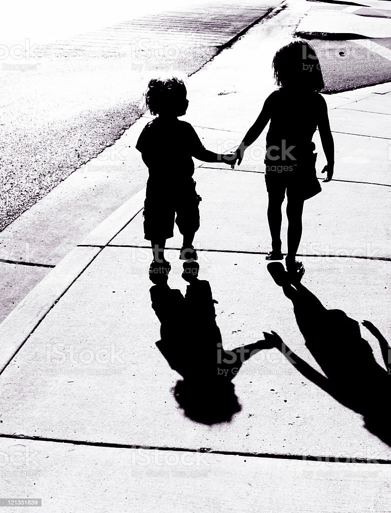 Adorable Children Silhouettes: Boy and Girl Holding Hands stock photo