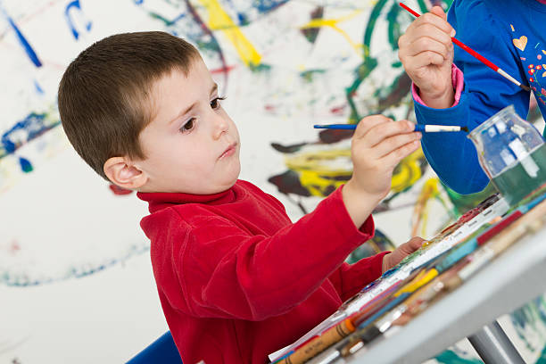 Adorable concentrated boy painting and drawing stock photo