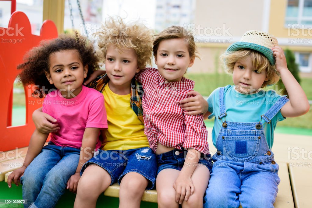 adorable curly boy embracing two multicultural children while other boy sitting near at playground royalty-free stock photo