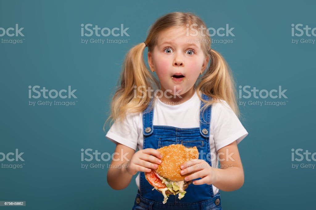 Adorable cute little girl in white shirt and jean jumpsuit with hamburger royalty-free stock photo