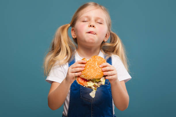 Adorable cute little girl in white shirt and jean jumpsuit with hamburger stock photo