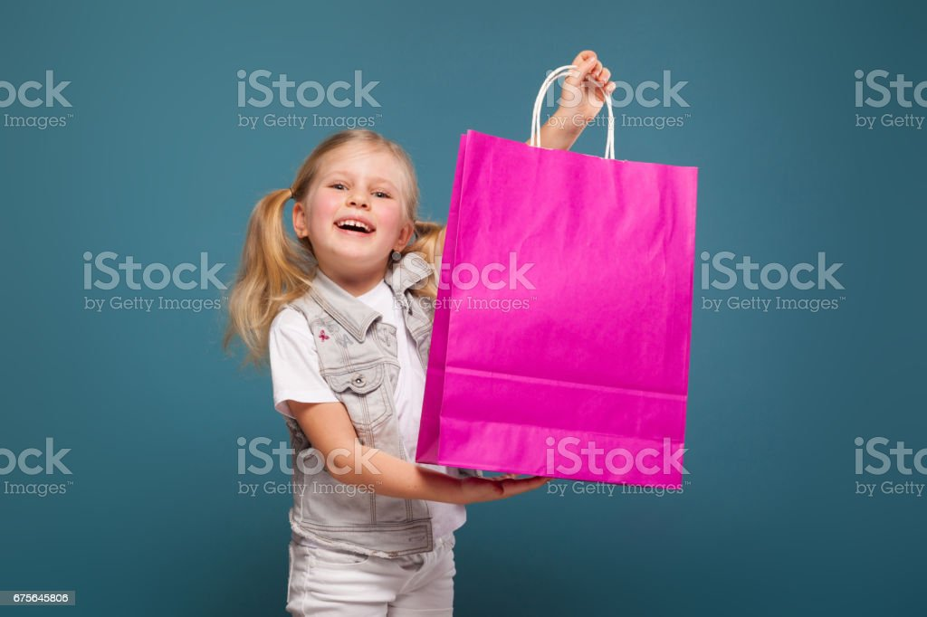 Adorable cute little girl in white shirt, white jacket and white trousers hold purple paper bag royalty-free stock photo