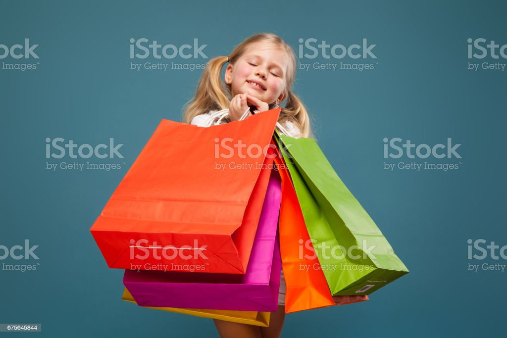 Adorable cute little girl in white shirt, white jacket and white shorts hold colorful paper bags royalty-free stock photo