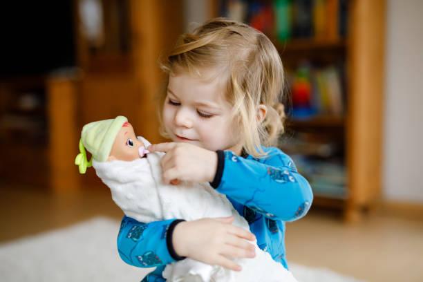 Entzückend niedlich niedlich kleine kleine kleine Mädchen mit Puppe spielen. Glückliches gesundes Baby, das Spaß am Rollenspiel hat, Mutter zu Hause oder im Kindergarten spielt. Aktive Tochter mit Spielzeug. – Foto