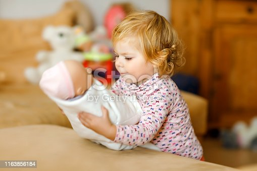 Adorable cute little toddler girl playing with doll. Happy healthy baby child having fun with role game, playing mother at home or nursery. Active daughter with toy