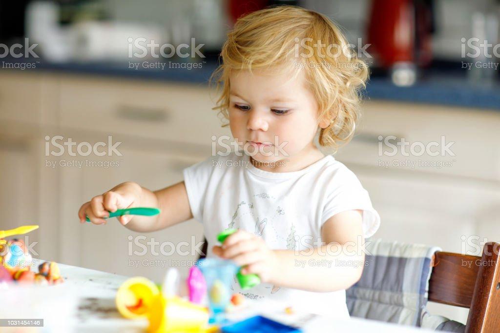 Entzückende niedliche kleine Kleinkind Mädchen mit bunten Ton. Gesundes Baby spielen und Spielzeug aus Salzteig zu schaffen. Kleines Kind Modelliermasse Formen und lernen – Foto