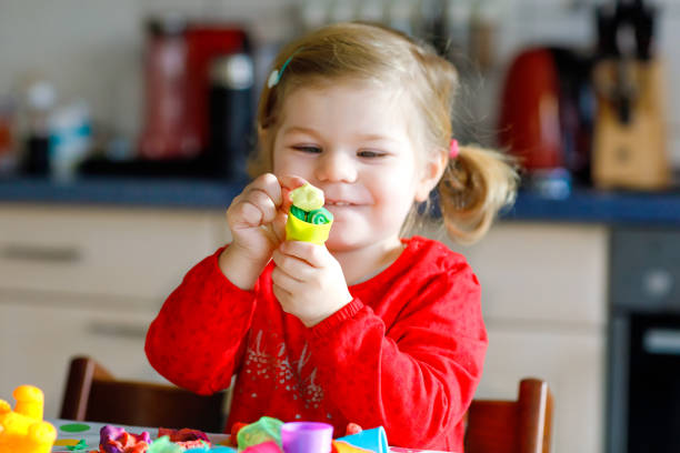 entzückende niedliche kleine kleinkind mädchen mit bunten ton. gesundes baby kind spielen und spielzeug aus salzteig zu erstellen. kleines kind modelliermasse formen und lernen - knete spiele stock-fotos und bilder