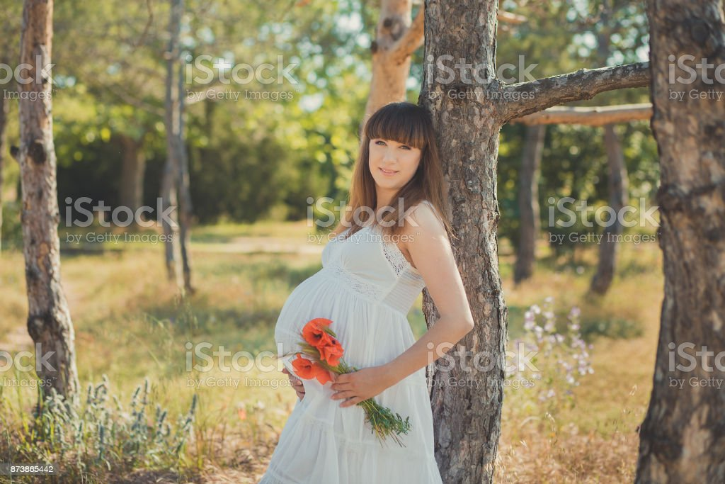 Adorable Cute Pregnant Lady Woman In White Airy Dress Posing Close To Tree In Forest Holding Tummy Abdomen Dreaming Attractive Beautiful Young Girl Enjoying Warm Summer With Unborn Child In Belly Stock