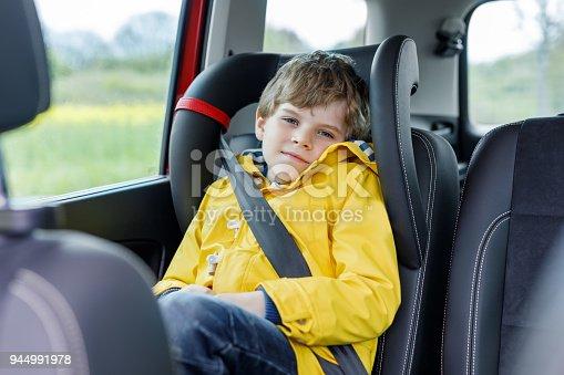 9c2089f8b istock Adorable cute preschool kid boy sitting in car in yellow rain coat.  944991978