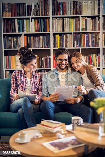 834814926 istock photo Adorable cute stylish high school student group sitting on the sofa and learning together in the library. 938313978