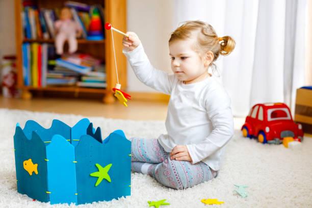 Entzückende niedliche kleine Mädchen spielen mit hölzernen Angeln Spiel zu Hause oder Kindergarten. Fröhliches Kindertraining Gedächtnisgrab mit Angelrute. Entwicklungs-und Koordinationsschritt und Ausbildung von Kindern. – Foto