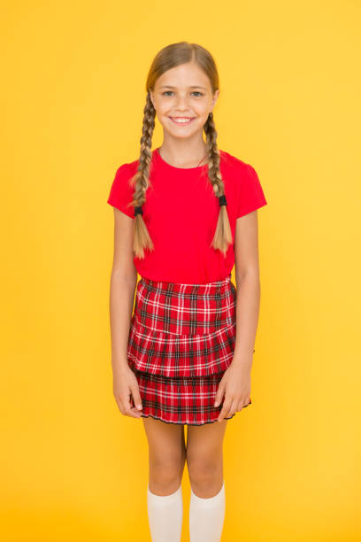 Adorable cutie. Cute little girl charming smile on yellow background. Happy small girl wearing red clothes. Girl with braided hair long braids. Adorable girl proud being pupil. Happy childhood stock photo